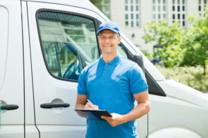 42544955 - young happy male worker in front of truck writing on clipboard