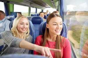 59227999 - transport, tourism, friendship, road trip and people concept - young women or teenage friends riding in travel bus